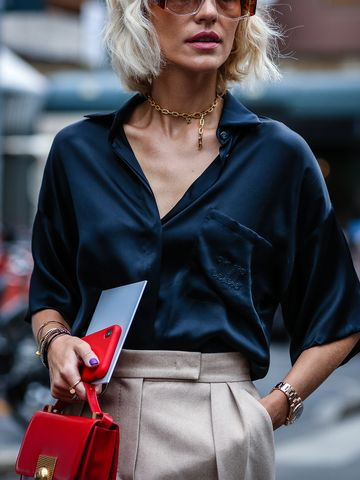 Women's outfit idea for 2021 with neutral smart trousers, red shoulder bag, metallic necklace. Suitable for spring and summer.