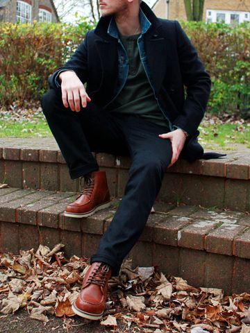 Men's outfit idea for 2021 with pea coat, dark denim jacket, green long-sleeved henley top, dark blue jeans, workboots. Suitable for spring, autumn and winter.