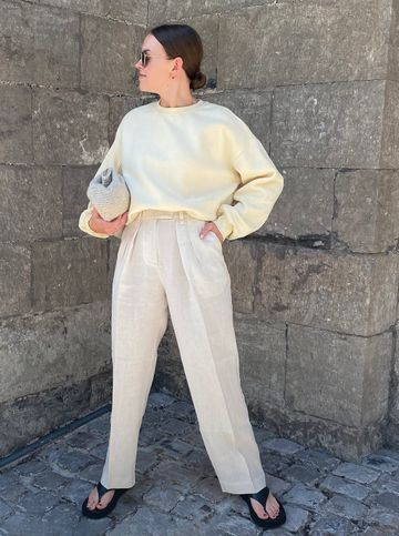 Women's outfit idea for 2021 with neutral sweatshirt, neutral casual trousers, black flat sandals. Suitable for spring.
