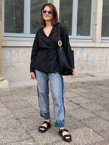 Women's outfit idea for 2021 with black top, blue jeans, metallic earring, black tote bag, black flat sandals. Suitable for spring and summer.