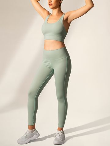 Women's outfit idea for 2021 with green sports bra, green sports leggings, white sock, white trainers. Suitable for spring, summer, autumn and winter.