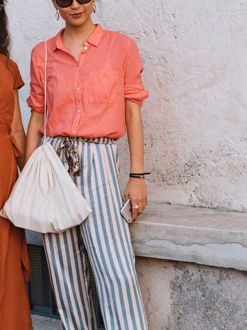 Women's outfit idea for 2021 with orange shirt, metallic flat sandals. Suitable for spring.