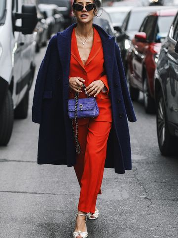 Women's outfit idea for 2021 with navy overcoat, red blazer, navy cami, red smart trousers. Suitable for spring and autumn.