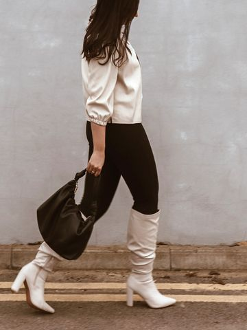 Women's outfit idea for 2021 with black tshirt, black jeans, black shoulder bag, white ankle boots. Suitable for spring and fall.