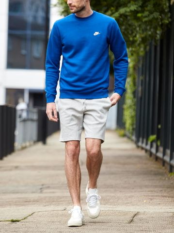 Men's outfit idea for 2021 with blue sweatshirt, sweat shorts, white trainers. Suitable for spring and summer.