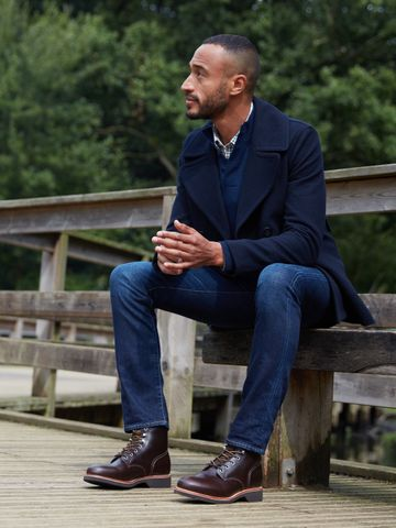 Men's outfit idea for 2021 with navy pea coat, half-zip / half-button jumper, dark blue jeans, lace-up leather boots. Suitable for autumn and winter.