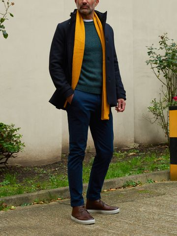 Men's outfit idea for 2021 with single-breasted overcoat, bold coloured crew neck jumper, navy chinos, plain bright knitted scarf, chukka boots. Suitable for autumn and winter.