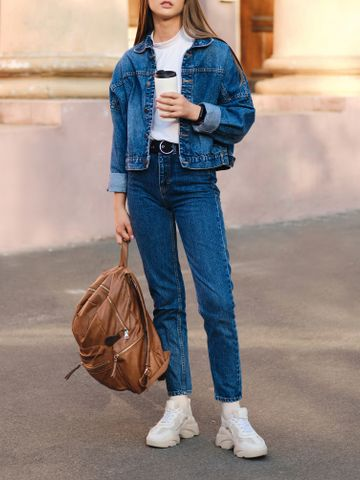 Women's outfit idea for 2021 with blue denim jacket, white tshirt, blue jeans, white trainers. Suitable for autumn.